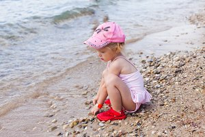 Pretty girl playing with sand on the