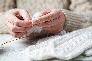 Woman knits winter warm clothes clos
