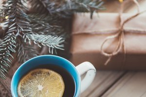 Mug with hot tea and lemon on a wood