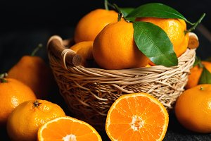 Tangerines in a wooden basket on a d