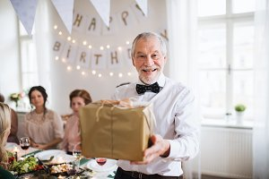 A senior man holding a present in a