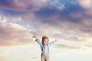 Kid pretending flying on a cloudy