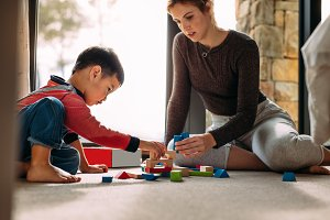 Mother and son playing with building