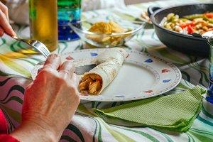 Woman rolling mexican fajita on the