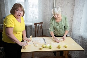 Two old women making little pies
