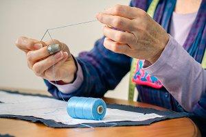 Senior female dressmaker threading a