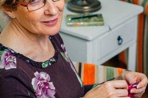 Portrait of woman knitting a wool sw