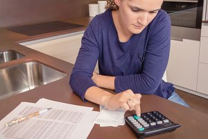 Woman with calculator review bills