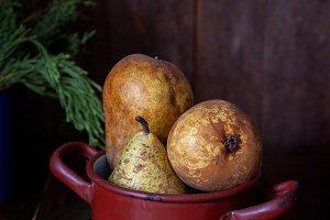 Very ripe pears and saucepan on rust