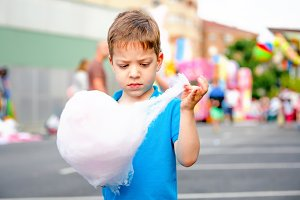Cute child eating pink cotton candy