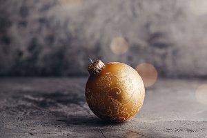 Gold Christmas ball on grey stone ba