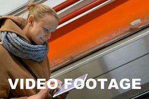 Woman on escalator using tablet