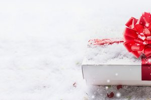 White gift box with red bow on snow