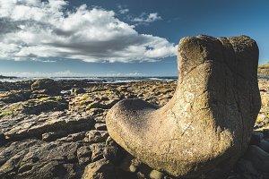 Close-up boulder on stone beach. Sky