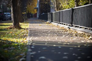 The fenced sidewalk is covered with