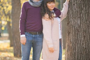 Loving couple stand near a tree in