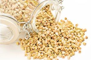 Raw green buckwheat in bank on white