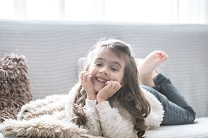 happy little girl lying on the couch