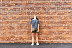 Girl looking up against brick wall