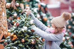 Little happy girl near fir-tree bran