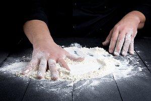 white wheat flour on a black wooden