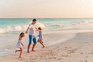 Family walking on white tropical bea