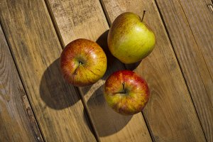 The apples lying on the wooden backg