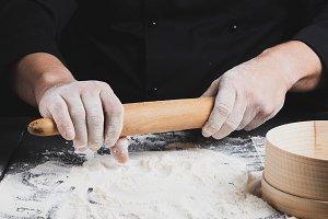 wooden rolling pin in men's hands