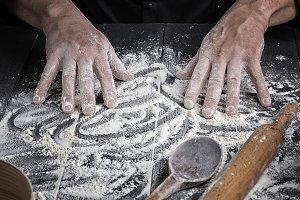 men's hands stir the wheat flour
