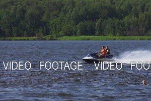 Riders on jet ski on lake.