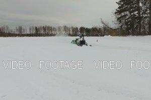 Racing on a snowmobile.