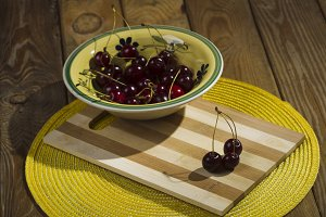Berries cherries in a bowl on a wood