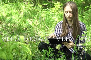 Girl uses a tablet in the woods.
