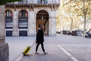 Young man walking with his suitcase