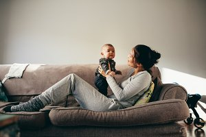 Woman sitting on couch with her baby