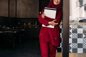 Muslim woman standing with laptop