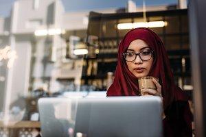 Hijab girl with coffee using laptop