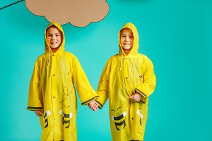 Twin sisters in raincoats