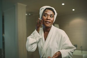 Female putting on moisturizer