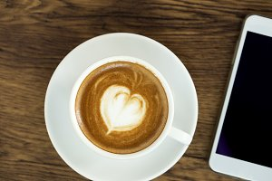 Smart phone with latte art coffee on