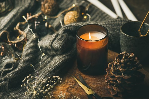 Candle on wooden board, sweater and