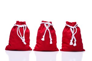 Three red Santa Claus Toy Bags on wh