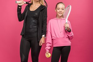 mother and daughter holding tennis r