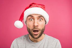 portrait of shocked man in santa hat