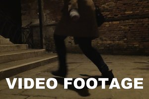 Woman running in dark alleyway