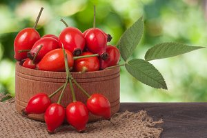 rosehips in wooden bowl on a table
