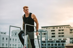 Fitness man climbing rooftop stairs