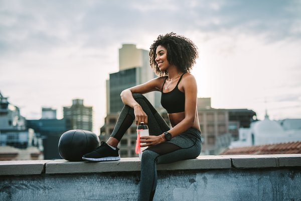 Fitness woman sitting on rooftop
