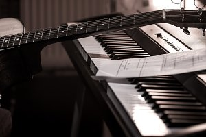 acoustic guitar stands on piano