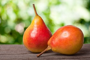 two pears on a dark wooden table